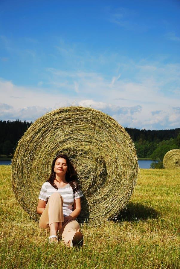 Frau, die nahe dem Strohballen sitzt lizenzfreies stockfoto