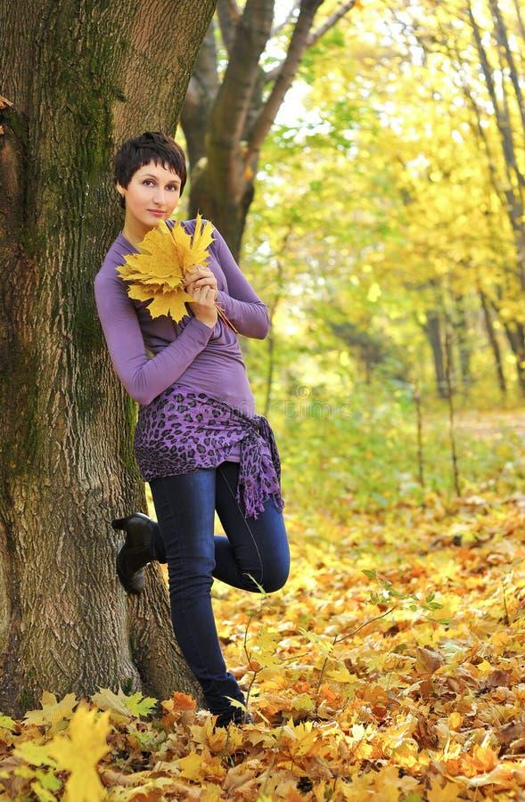 Frau, die nahe einem Baum hält einen Blumenstrauß von Ahornblättern steht lizenzfreies stockfoto