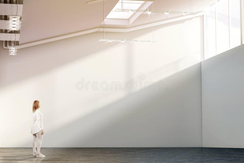Frau, die nahe leerem weißem Wandmodell in der modernen Galerie geht stockbilder