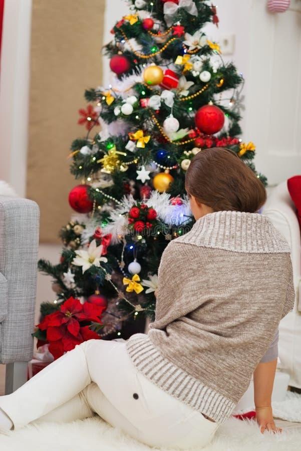 Download Frau, Die Nahe Weihnachtsbaum Sitzt. Hintere Ansicht Stockbild - Bild von dekorationen, jahreszeit: 27728189