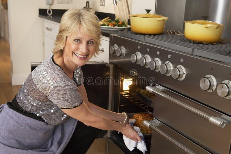 Frau, die Nahrung aus dem Ofen heraus nimmt stockbild
