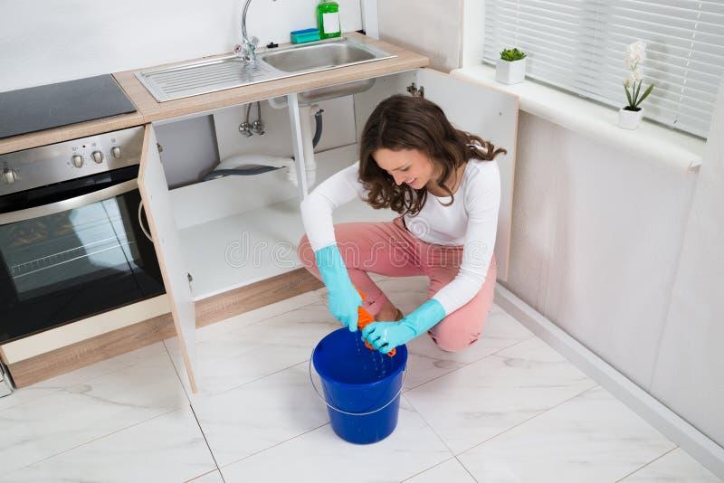 Frau, die nassen Lappen am Küchen-Raum zusammendrückt stockfotografie