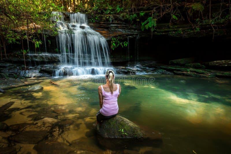 Frau, die Natur genie?t Geschecktes Sonnenlicht am Wasserfallfelsenpool lizenzfreie stockfotografie