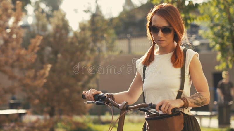 Frau, die neben Reitfahrrad auf Stadtpark geht Frauenfahrradpark lizenzfreie stockfotos