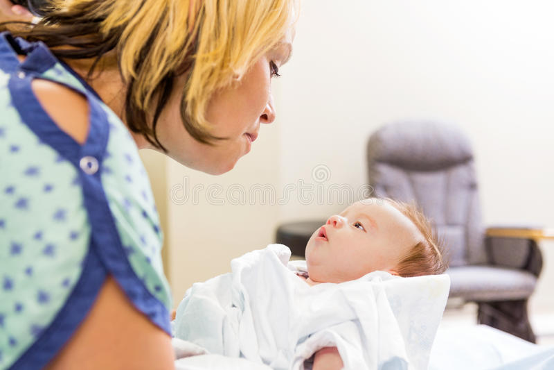 Frau, die nettes neugeborenes Babygirl im Krankenhaus betrachtet stockfotos