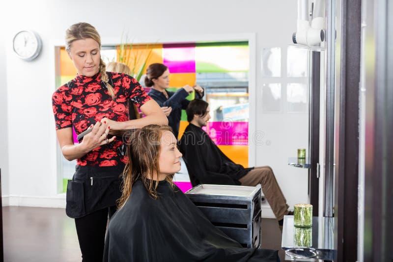 Frau, die neuen Haarschnitt durch Herrenfriseur am Wohnzimmer erhält stockbild