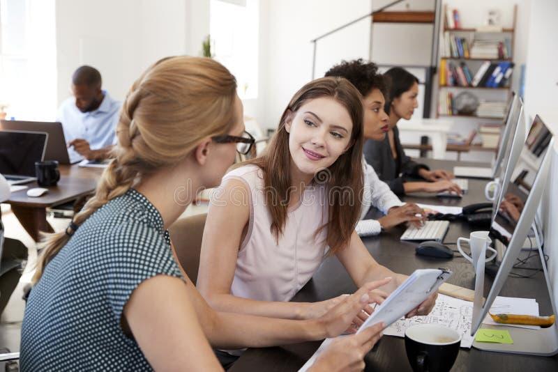 Frau, die neuen weiblichen Angestellten in einem Bürogroßraum ausbildet lizenzfreies stockfoto