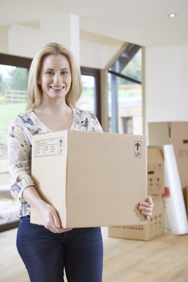 Frau, die in neues Haus mit Verpackungs-Kasten umzieht stockfotografie