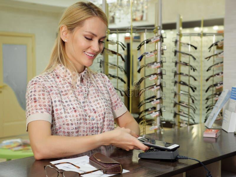 Frau, die NFC-Technologie für Zahlung im Shop einsetzt stockfotos