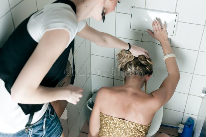Frau, die oben in die Toilette wirft stockfoto