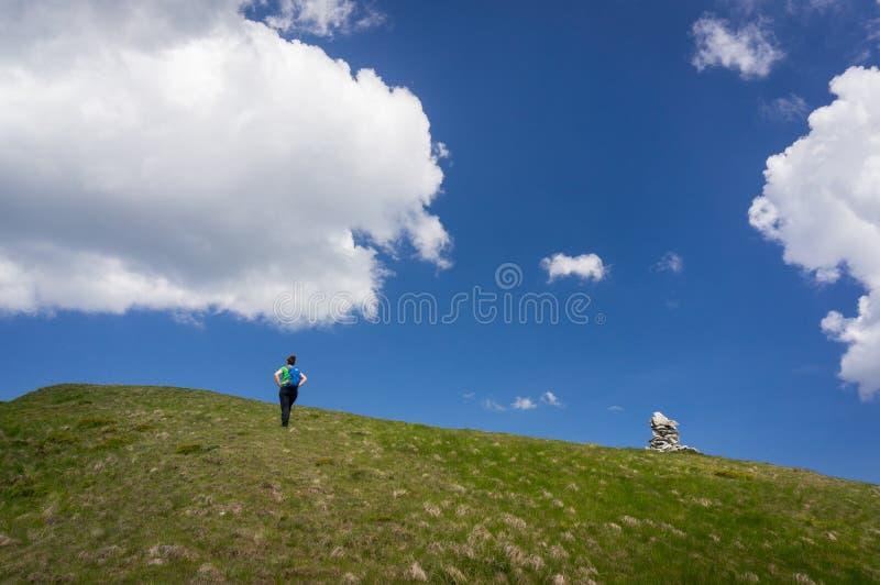 Frau, die oben eine Steigung wandert stockbild