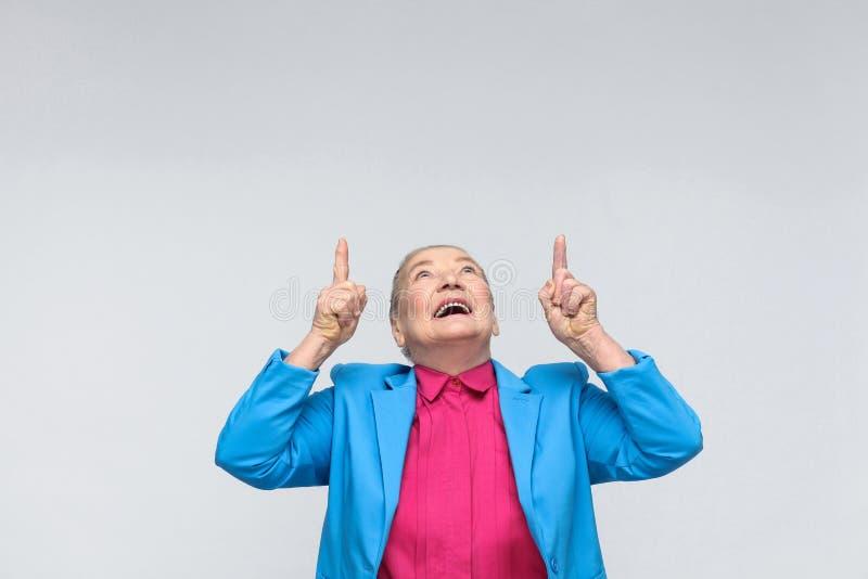 Frau, die oben Finger auf Kopienraum und das toothy Lächeln zeigt lizenzfreies stockbild
