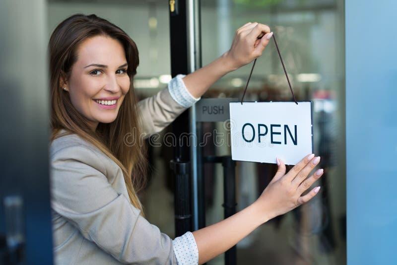 Frau, die offenes Zeichen auf Tür hängt lizenzfreies stockfoto