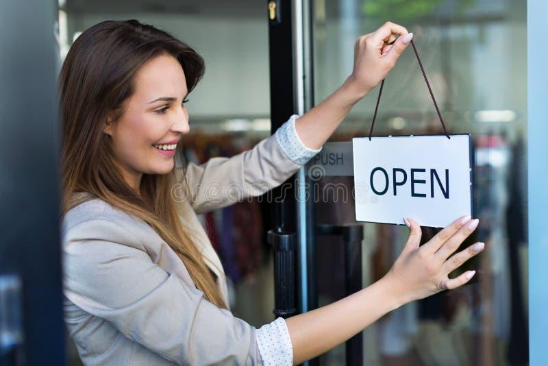 Frau, die offenes Zeichen auf Tür hängt stockfotografie
