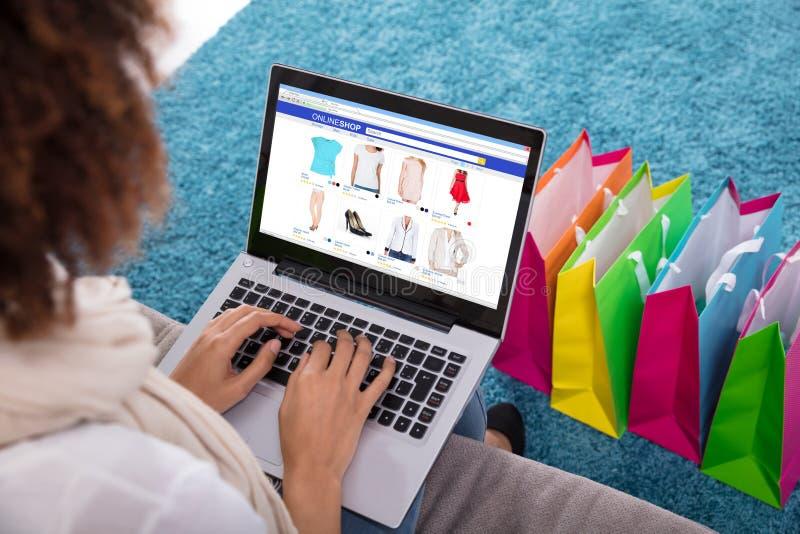 Frau, die online auf Laptop kauft stockfoto