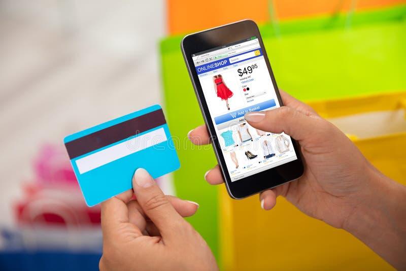 Frau, die online auf Smartphone kauft stockfotos