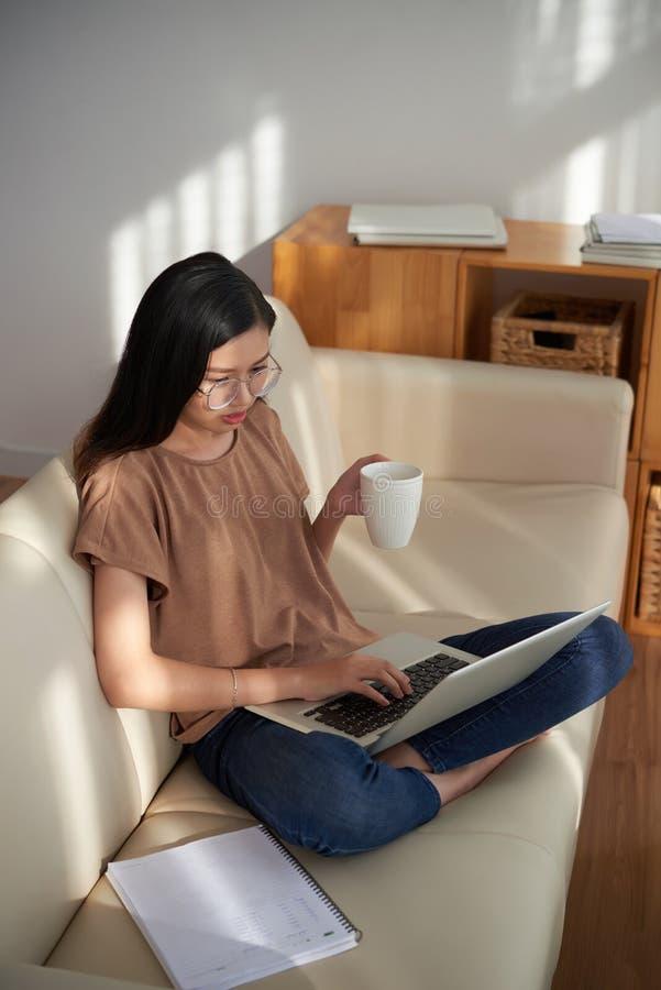 Frau, die online zu Hause arbeitet lizenzfreies stockfoto