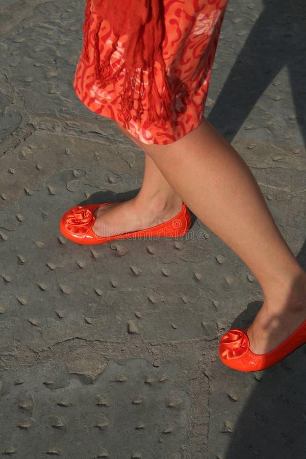 Frau, die orange Kleider- und Leuchtorangeschuhe trägt lizenzfreies stockfoto