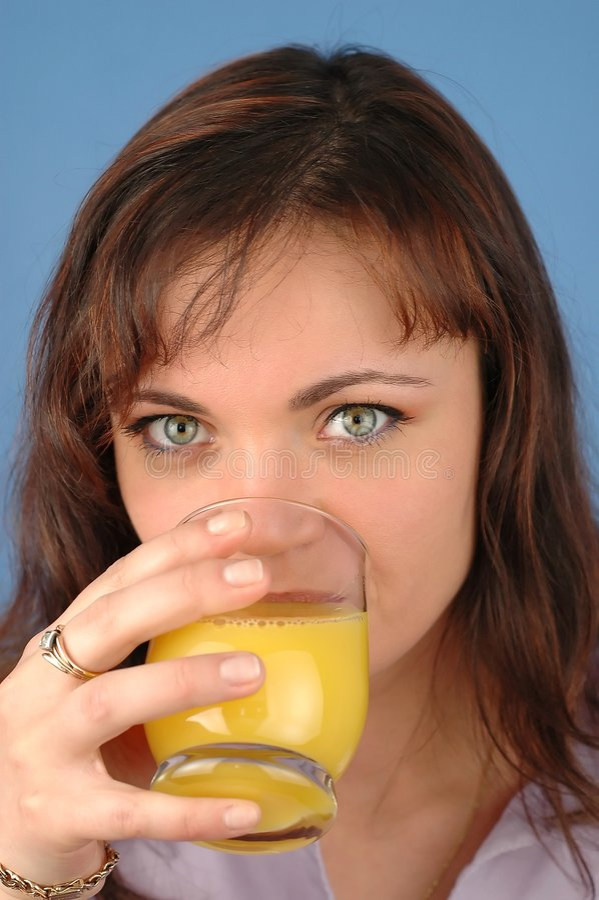 Frau, die Orangensaft trinkt stockfotografie