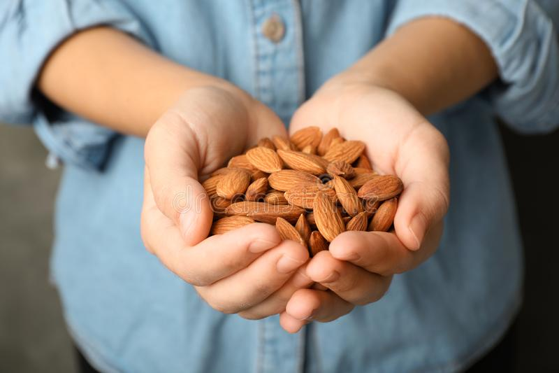 Frau, die organische Mandelnüsse in den Händen hält stockfotografie