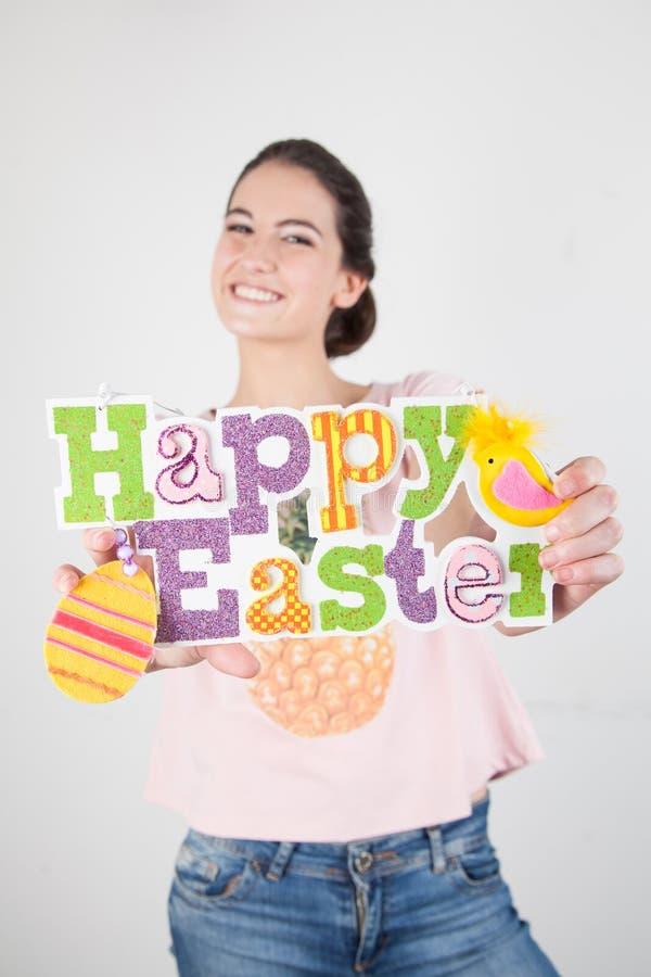Frau, die Ostern hält ein Plakat feiert stockfotografie