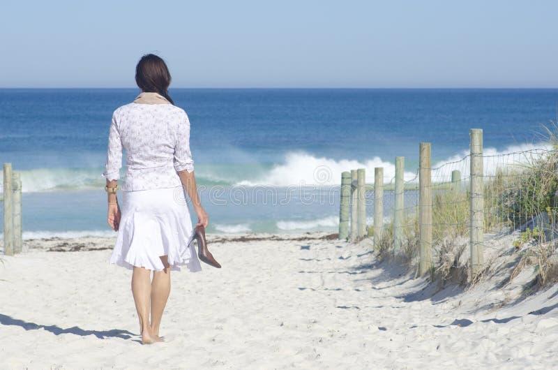 Frau, die in Ozean auf den Strand setzen geht stockfotos