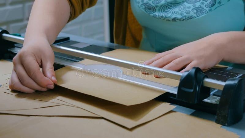 Frau, die Papierschneidemaschine, Guillotine, Designerarbeiten verwendet lizenzfreie stockfotografie