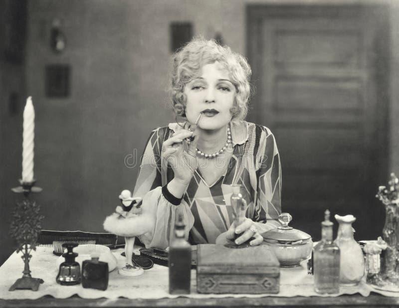 Frau, die Parfüm auf ihre Lippen zutrifft stockbilder