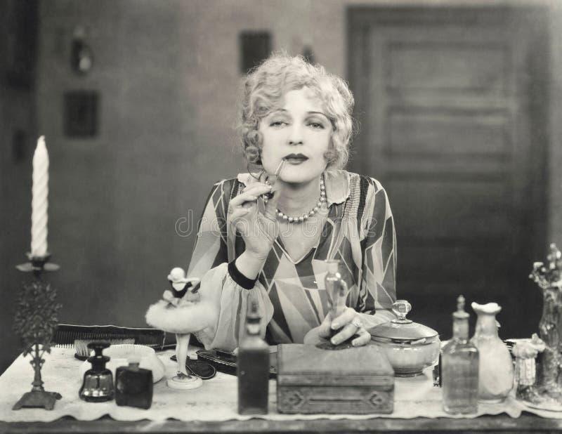 Frau, die Parfüm auf ihre Lippen zutrifft lizenzfreies stockbild