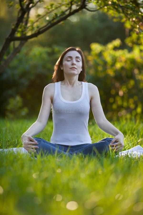 Frau, die am Park meditiert stockfotografie