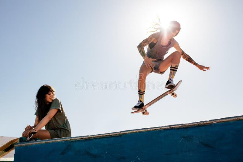 Frau, die am Park mit dem Freund sitzt auf Rampe Skateboard fährt lizenzfreie stockfotos