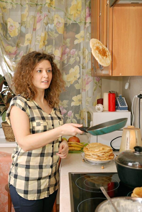 Frau, die Pfannkuchen kocht lizenzfreie stockfotos