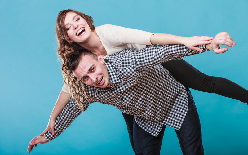 Frau, die piggyback auf Mann fährt Glückliche Paare stockfotografie