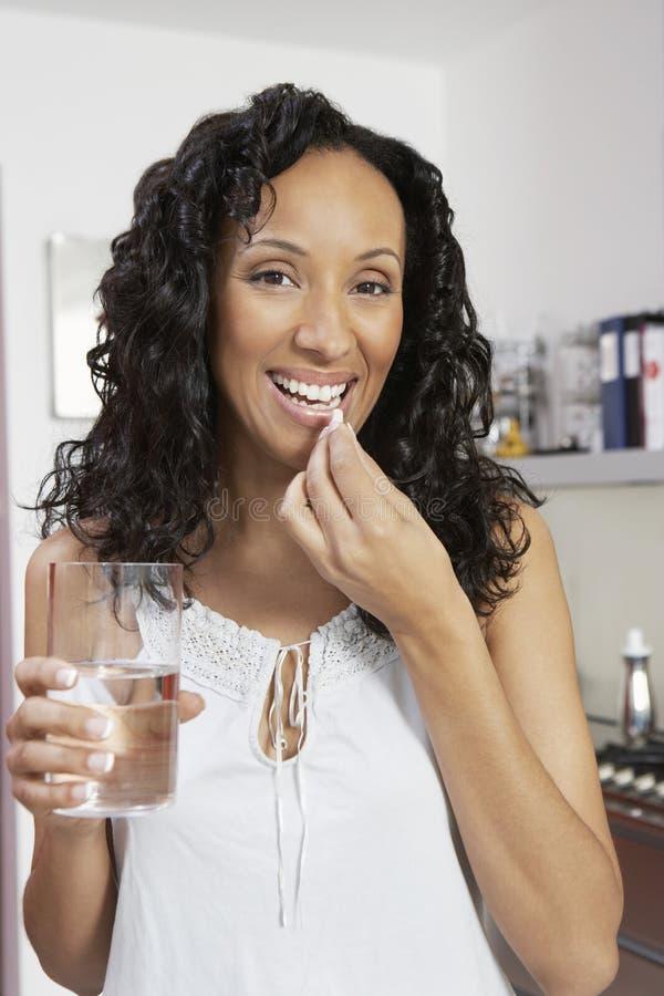 Frau, die Pille mit Wasser einnimmt lizenzfreies stockbild