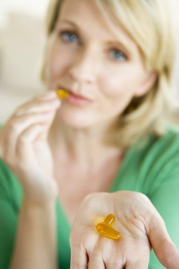 Frau, die Pillen nimmt stockbild