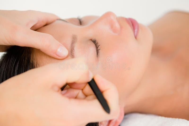 Frau, die Pinzette auf geduldiger Augenbraue verwendet stockfotografie