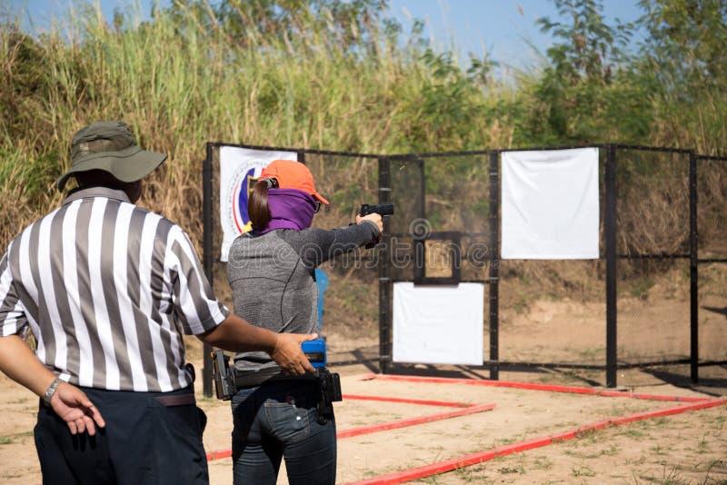 Frau, die Pistole im Schießstand für Wettbewerb zielt stockfotografie