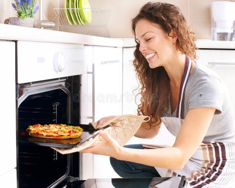Frau, die Pizza kocht stockbilder