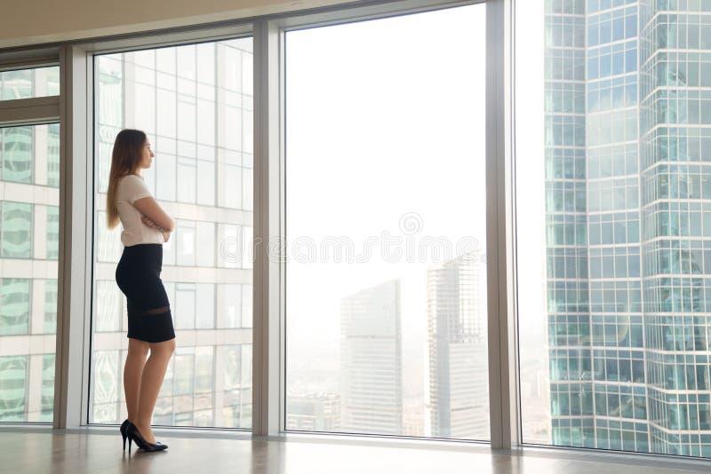 Frau, die an Pläne auf zukünftigem nahem Fenster denkt lizenzfreies stockbild