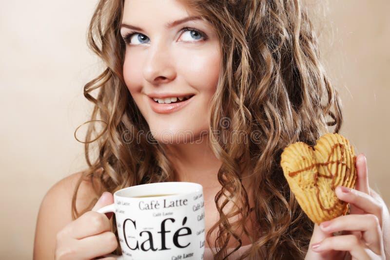 Frau, die Plätzchen isst und Kaffee trinkt. lizenzfreie stockfotos