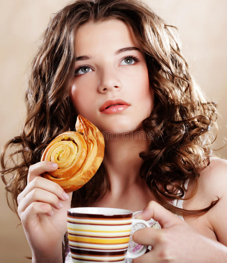 Frau, die Plätzchen isst und Kaffee trinkt. stockbild