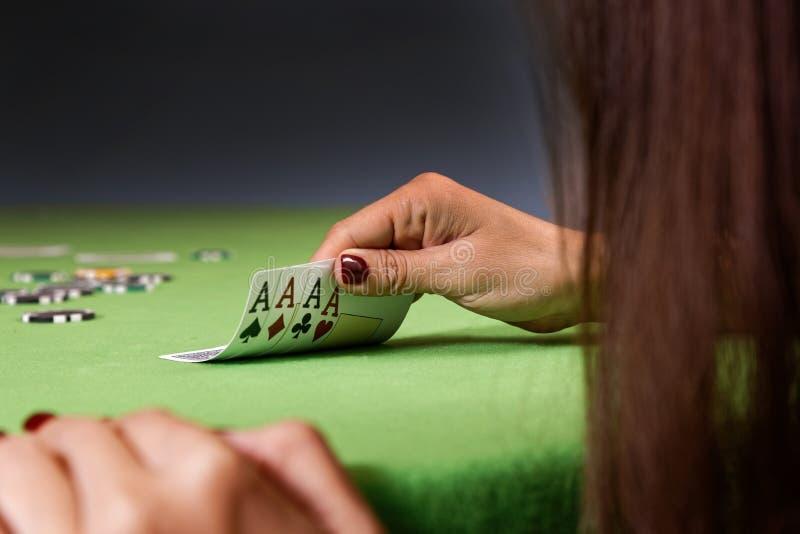 Frau, die Pokerspiel spielt und Karten betrachtet Grüne Tabelle, Chips und vier Askarten in der Hand stockfoto