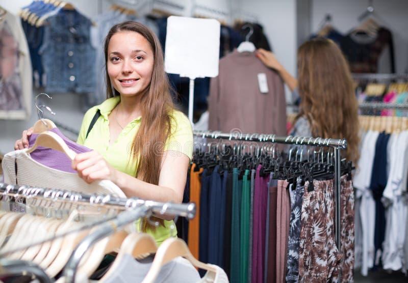 Frau, die Pullover im Shop wählt stockfoto