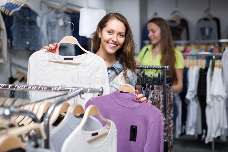 Frau, die Pullover im Shop wählt stockfotos