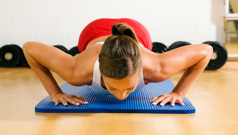 Frau, die Pushups in der Gymnastik tut
