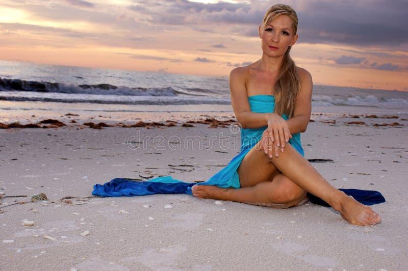 Frau, die queresmit beinen versehenes auf Strand sitzt lizenzfreie stockbilder