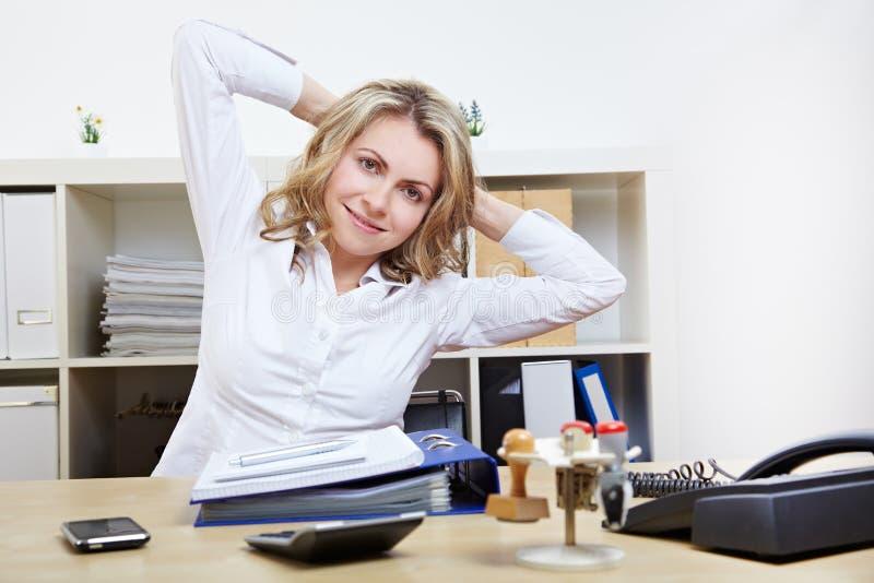 Frau, die Rückenübungen bei der Arbeit tut stockfotografie