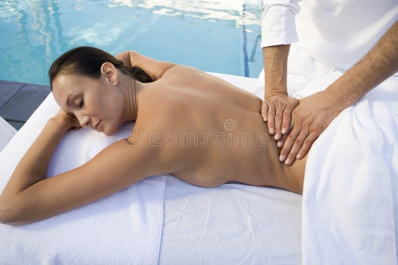 Frau, die Rückenmassage durch Pool empfängt lizenzfreies stockfoto