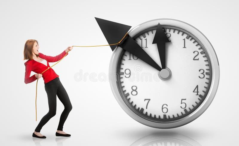 Frau, die rückwärts Uhrhände zieht stockbild