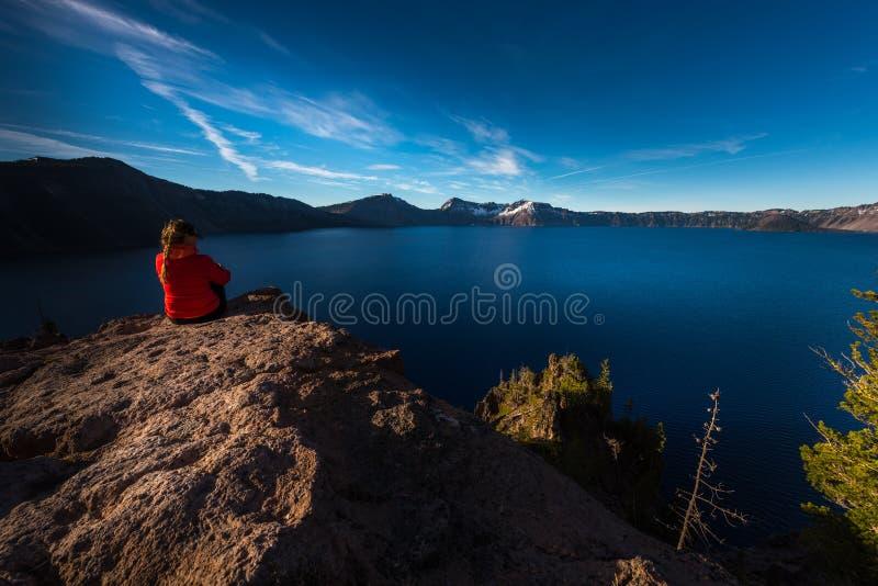 Frau, die am Rand einer Klippe betrachtet Crater See Oreg sitzt stockfoto